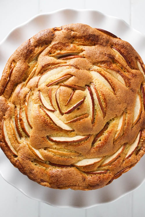 Top view of Russian sharlotka apple cake decorated with sliced apples.