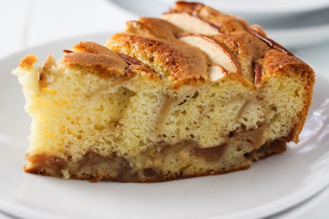 Side view of a slice of sharlotka, Russian apple cake, studded with apples and cinnamon.