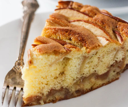 Close up of a slice of sharlotka, Russian apple cake on a white plate with a vintage fork.