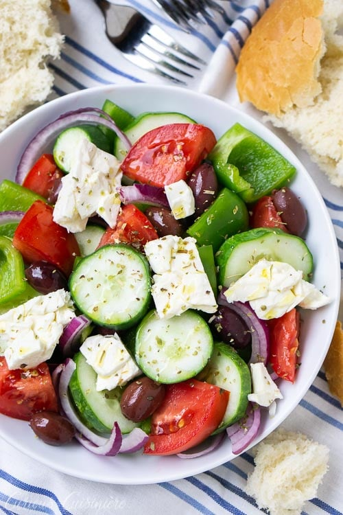 Overheat image of a traditional Greek salad (Horiatiki) is a chunky salad that combines fresh summer produce, salty olives, and creamy goat cheese with a light oil and vinegar dressing.