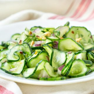 Thinly sliced cucumber with red onion sand peanuts - horizontal image.