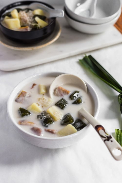 Bubur Cha Cha, a creamy and sweet Malaysian dessert made from yam, taro, and coconut milk in a white bowl with a pandan leaf.