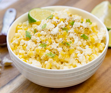 A bowl of Esquites Mexican street corn salad topped with a lime wedge and queso fresco cheese and chili powder