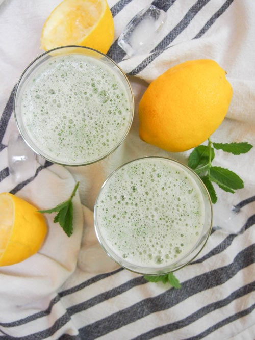 Overhead image of two frothy glasses of Limonana Middle Eastern Mint Lemonade.
