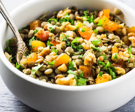 Mshosh Armenian lentil salad with apricots, and walnuts with a fork.