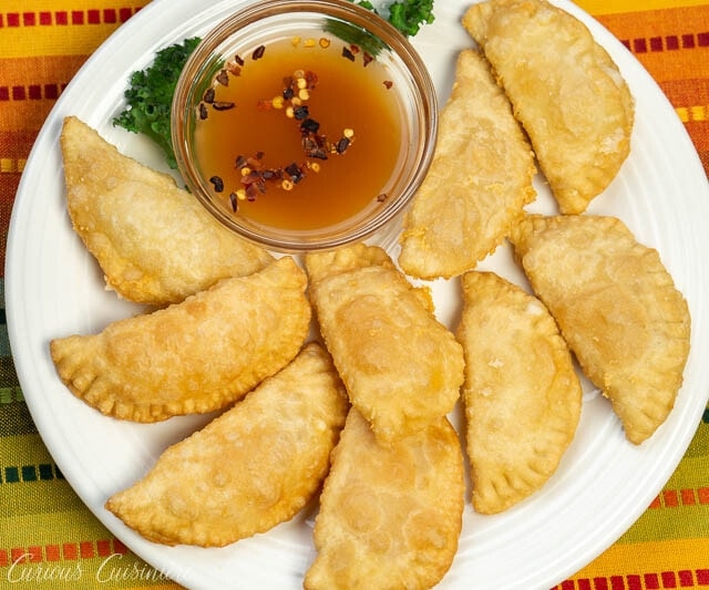 Brazilian Pastel de Queijo (Cheese Pastries) on a plate with hot sauce, overhead image
