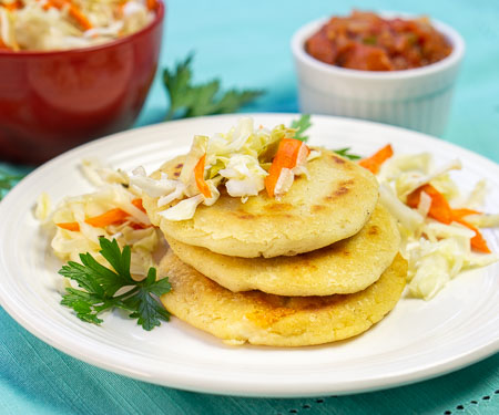 El Salvadoran pupusas, cheese stuffed tortillas, stacked with cabbage slaw on top small image