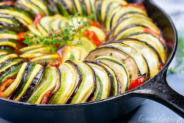 Up close pan shot of layered ratatouille in a cast iron skillet