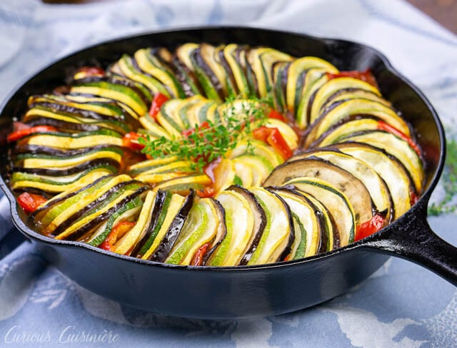 Whole pan shot of baked layered ratatouillewith eggplant, summer squash, zucchini, tomatoes, and red peppers.
