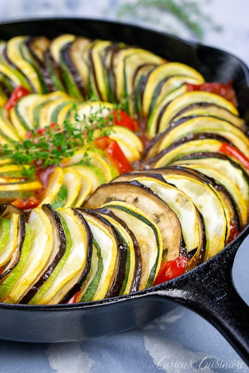 Skillet shot of baked layered ratatouillewith eggplant, summer squash, zucchini, tomatoes, and red peppers.