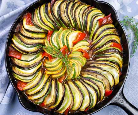Overhead image of layered ratatouille in a cast iron skillet with eggplant, summer squash, zucchini, tomatoes, and red peppers.