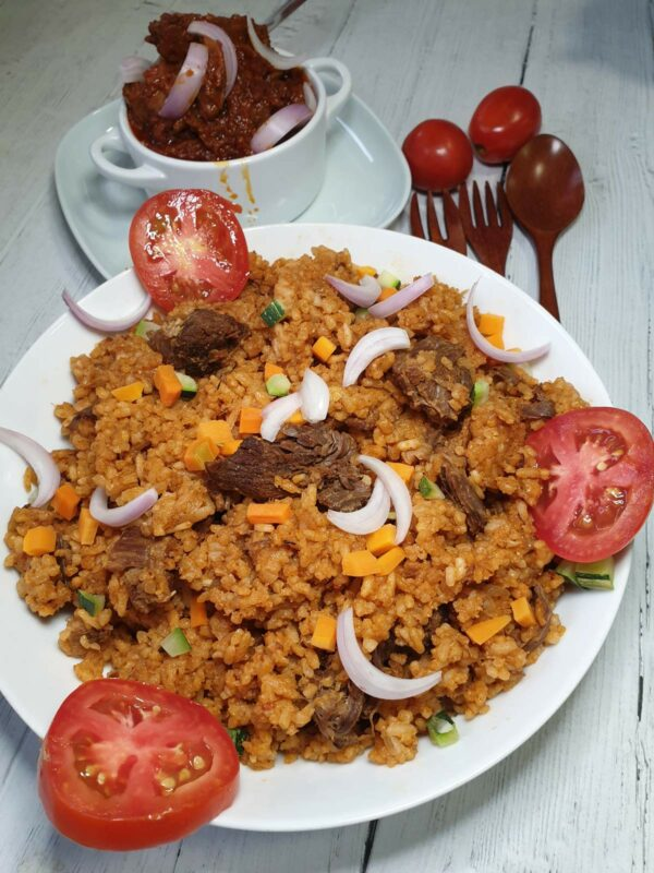 Ghanaian Jollof Rice with lamb garnished with onions